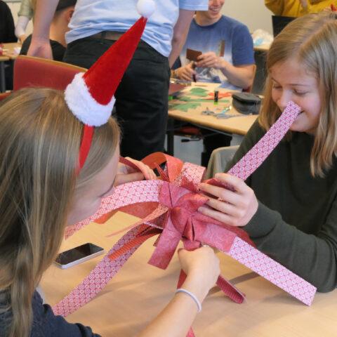To piger fletter en stor julestjerne